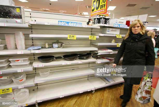 A woman walks past empty shelves at a Woolworths store in Chelmsford Essex as the company struggles to find a buyer for its chain of stores