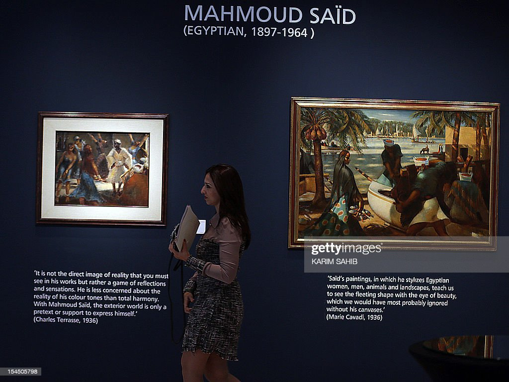 A woman walks past ' Fishermen in Rashid' (R) painting of the father of modern Egyptian art, Mahmoud Said on show at Christie's Auction house in Dubai on October 21, 2012, prior to the sale of modern and contemporary Middle Eastern art including Turkish and Iranian pieces to be auctioned on October 23 and 24.