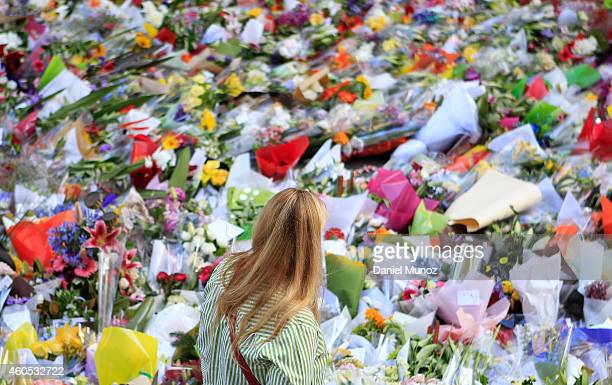 A woman walks past flowers placed by people as a mark of respect for the victims of Martin Place siege on December 16 2014 in Sydney Australia Sydney...