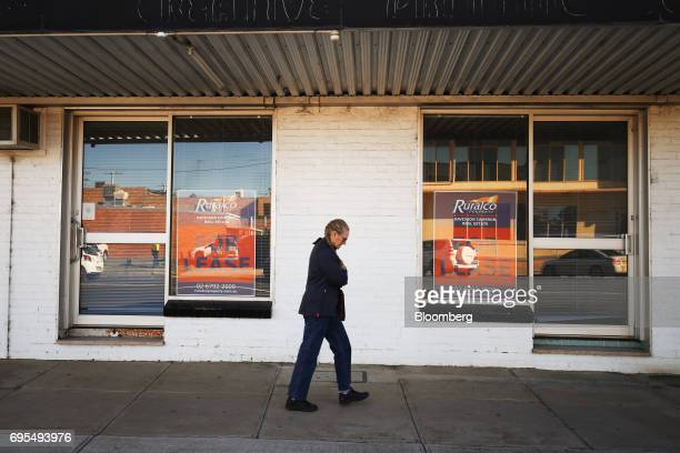 A woman walks past 'For Lease' signs displayed in the windows of a vacated property in Narrabri Australia on Friday May 26 2017 A decade after the...