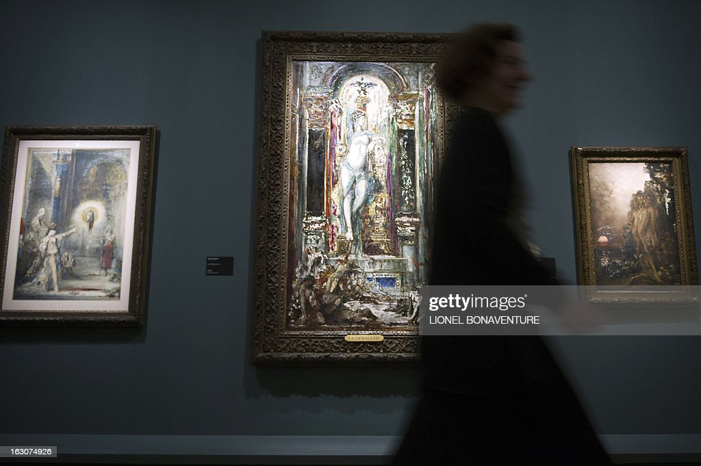 A woman walks past (From L) 'Galatee', 'La Debauche' and 'Les Sirenes' paintings by Gustave Moreau during the exhibition 'The Angel of the Odd. Dark Romanticism from Goya to Max Ernst' at the Orsay museum in Paris, on March 4, 2013. The exhibition will run from March 5 until June 9, 2013.