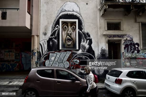 A woman walks past graffiti by a Bali born street artist WD in central Athens on October 11 2017 An ongoing exhibition devoted to 'Artists in Athens...