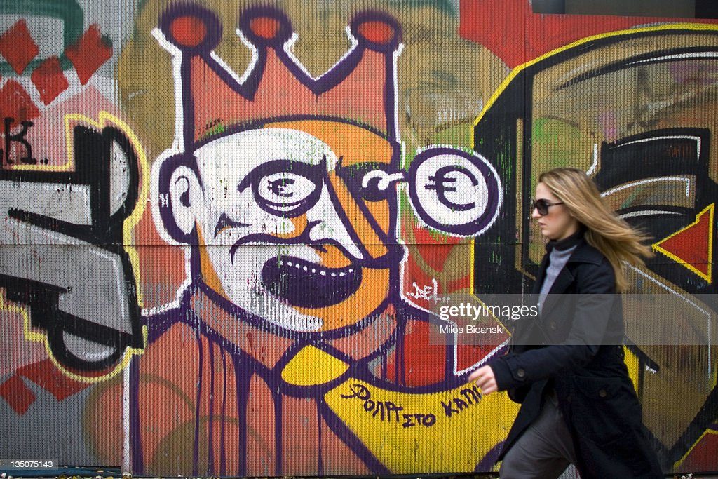A woman walks past graffiti displayed on a building on December 6, 2011 in Athens, Greece. Graffiti artists throughout the city are expressing the effects of austerity measures that have plagued the community as Greece continues to struggle in debt while lawmakers today are set to pass next year's budget.