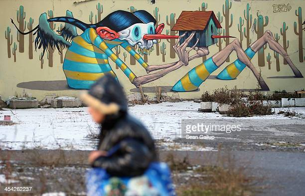 A woman walks past graffiti on December 7 2013 in Sofia Bulgaria Restrictions on the freedom of Bulgarians and Romanians to work in the European...