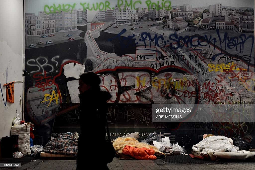 A woman walks past homeless people sleeping outside a metro station in central Athens on January 8, 2013. With low temperatures hitting Greece's capital, municipal officials have opened few temporary shelters for people sleeping rough during the cold snap.