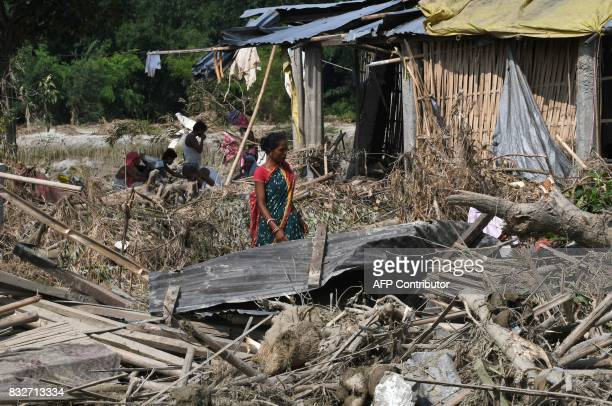 A woman walks past houses damaged by flood in Itahari Sunsari district some 250 kms from Nepal's capital Kathmandu on August 16 2017 At least 221...