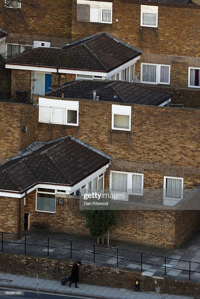A woman walks past housing near Herne Hill on January 30, 2013 in London, England. According to a report from independent analysts Oxford Economics, the average mortgage deposit for first-time buyers in London, is likely to exceed £100,000 GBP by 2020.