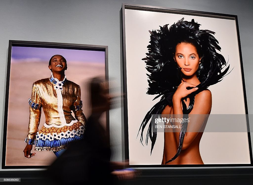 A woman walks past images by Patrick Demarchelier entitled 'Gilt-Laden' of Naomi Campbell 1987 (L) and 'Coque Feathers' of Christy Turlington 1987 (R) as part of the 'Vogue 100 a Century of Style' exhibition at the National Portrait Galley in central London on February 10, 2016. The exhibition showcases a range of photography commissioned by British Vogue since it was founded in 1916. / AFP / BEN STANSALL / RESTRICTED TO EDITORIAL USE - MANDATORY MENTION OF THE ARTIST UPON PUBLICATION - TO ILLUSTRATE THE EVENT AS SPECIFIED IN THE CAPTION