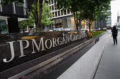A woman walks past JP Morgan Chase's corporate headquarters on August 12 2014 in New York City US banks announced second quarter profits of more than...