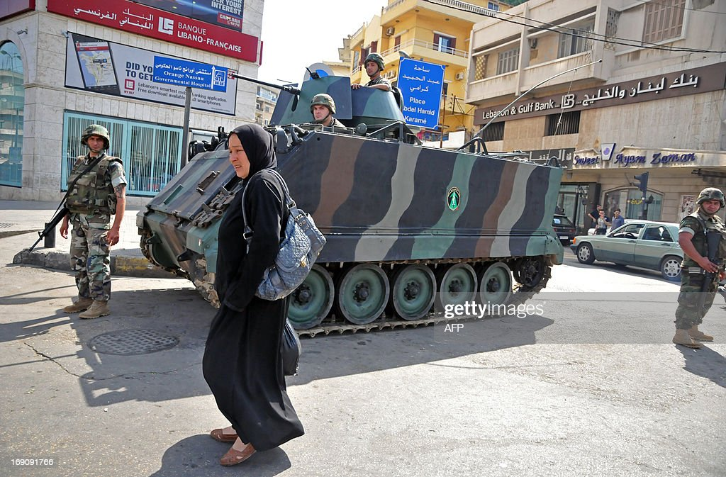 A woman walks past Lebanese soldiers standing guard with an armoured personnel carrier (APC) in the northern Lebanese city of Tripoli on May 20, 2013 following running gun battles the previous day between pro- and anti- Syrian government supporters. Violence broke out between members of the largely Sunni city and a small community of Alawites, an offshoot of Shite Islam to which Syrian President Bashar al-Assad belongs, as Syrian troops launched an assault against the rebel stronghold of Qusayr, in Syria's central province of Homs.