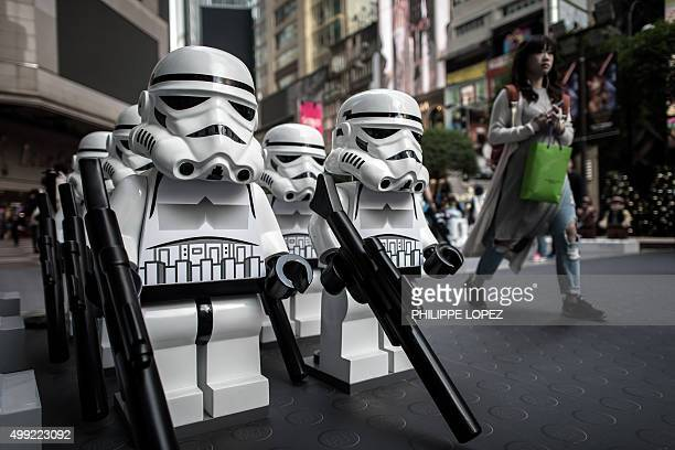 A woman walks past lego Star Wars models displayed outside a shopping mall in Hong Kong on November 30 2015 The new Star Wars movie titled 'The Force...