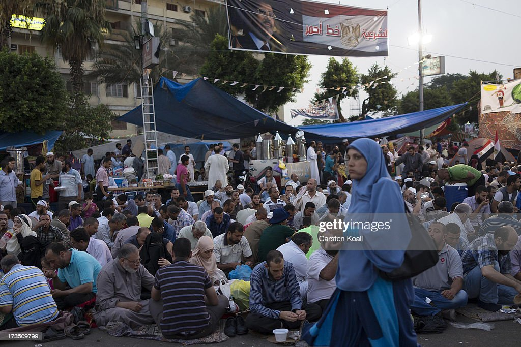 A woman walks past members of the Muslim Brotherhood and supporters of ousted president Mohamed Morsi pray at a rally outside Rabaa al-Adawiya mosque on July 15, 2013 in Cairo, Egypt. Senior US official William Burns has arrived in Egypt for the first time since the overthrow of Mohamed Morsi.