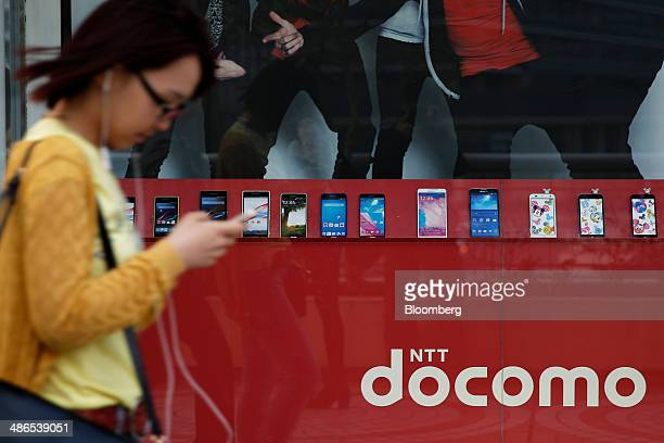A woman walks past mockup smartphones for NTT Docomo Inc on display at an electronics store in Tokyo Japan on Thursday April 24 2014 Docomo plans to...