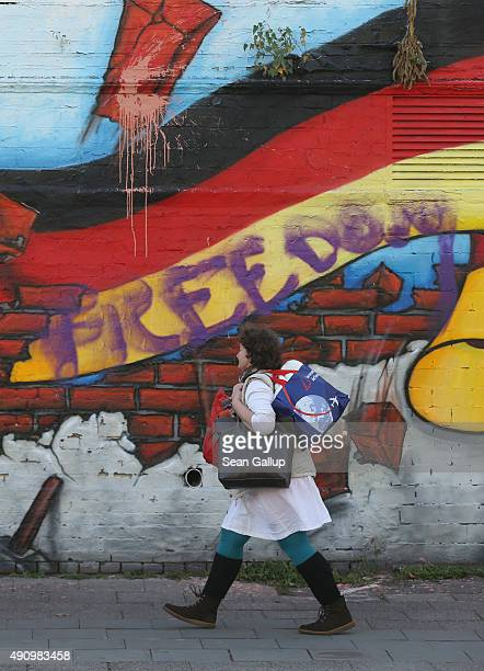 A woman walks past murals showing the German flag on the day before the 25th anniversary of German reunification on October 2 2015 in Berlin Germany...