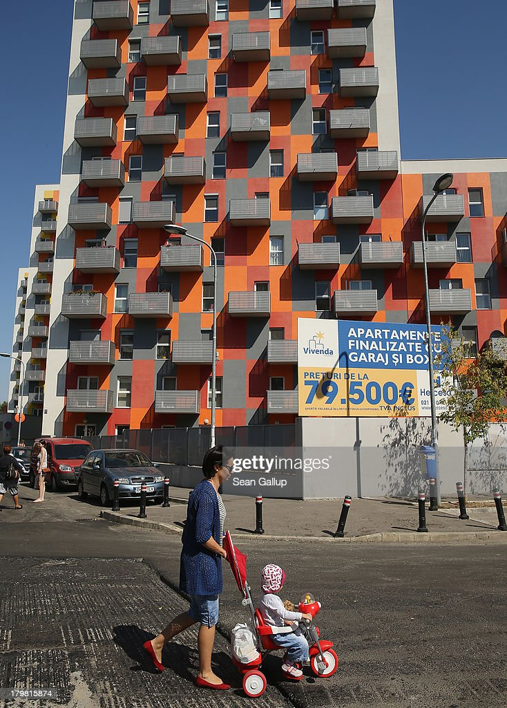 A woman walks past newly-built apartment buildings that are part of the Vivenda real estate development project on September 7, 2013 in Bucharest, Romania. While Romania's economic output has risen significantly since it joined the European Union in 2007, it still lags in infrastructure development and the fight against corruption.