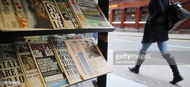 A woman walks past newspapers displayed on a stand in a newsagent on November 28 2012 in London England The findings of the Leveson Inquiry which...