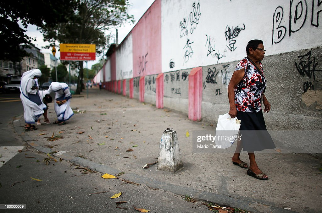 A woman walks past nuns during a procession near the Nossa Senhora da Penha Church on the final day of the annual October feast of the patron saint marking the 378th anniversary of the church on October 27, 2013 in Rio de Janeiro, Brazil. Pilgrims often climb the entire 382 steps that lead to the church, originally constructed in 1635, which is perched on a rocky hill. Brazil holds more Catholics than any other country.