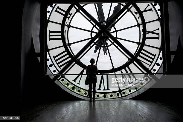 A woman walks past one of the clocks of the Orsay museum on May 18 2016 in Paris / AFP / MARTIN BUREAU