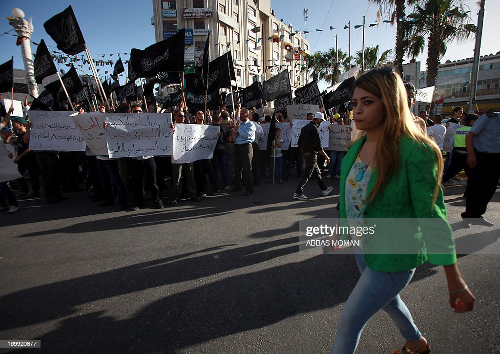 A woman walks past Palestinian supporters of Hizb utTahrir or the Islamic Liberation Party as they chant slogans and wave black and white flags with...