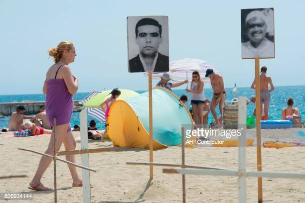 A woman walks past photographs of a dead migrants on Barcelona's Bogatell beach during an action called by pro human rights organizations 'Tanquem...