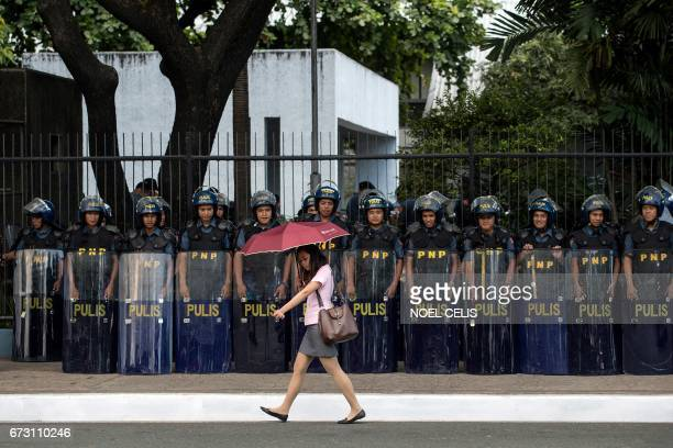 A woman walks past police standing in formation near the venue of the Association of Southeast Asian Nations summit off Manila Bay on April 26 2017...