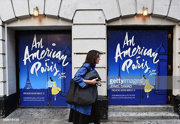 A woman walks past posters of a musical show 'An American in Paris' displayed on the side of the Palace Theater in New York on April 12 2015 during...