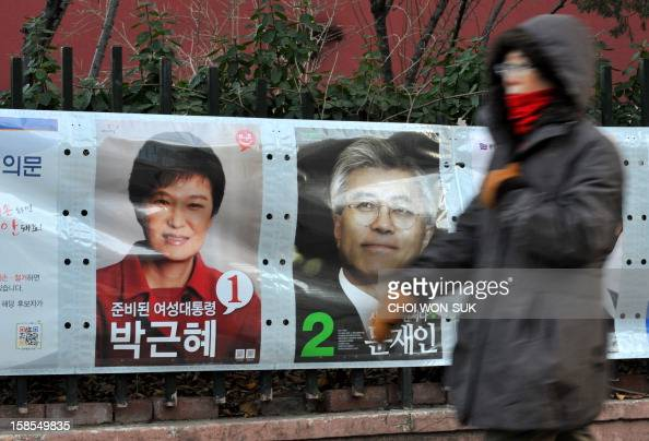 A woman walks past posters of South Korea's presidential candidates Park GeunHye of the ruling New Frontier Party and Moon JaeIn of the opposition...