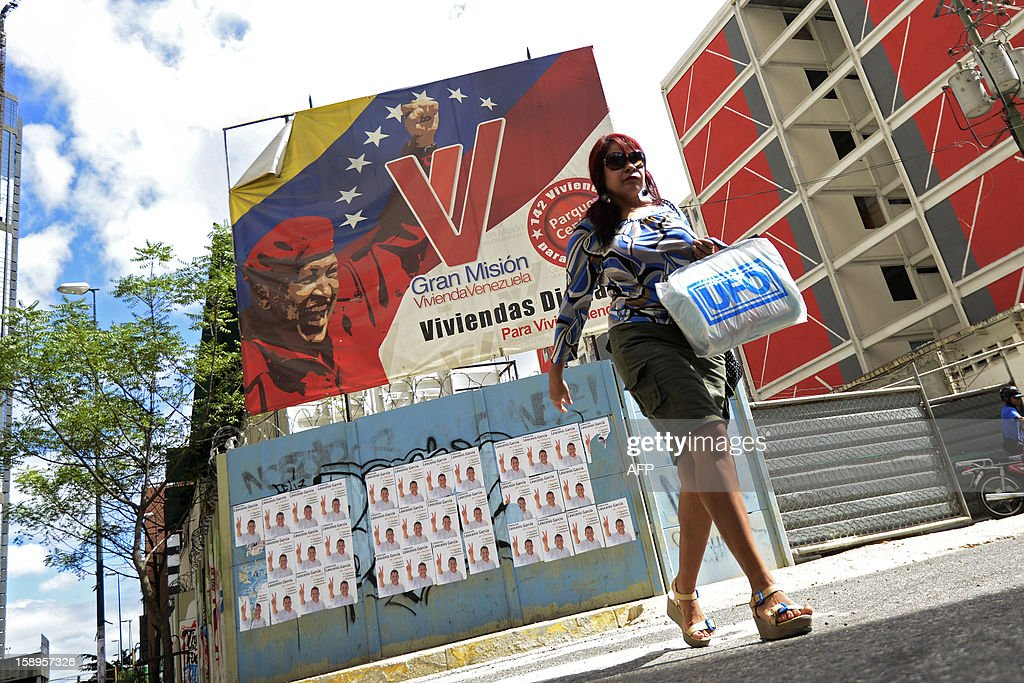 A woman walks past posters of Venezuelan President Hugo Chavez in Caracas on January 4, 2013. Hugo Chavez's top aides have gone on the offensive, accusing the opposition and media of waging a 'psychological war,' as Venezuela's cancer-stricken president battles a serious lung infection. The closing of ranks followed a high-level gathering of top Venezuelan officials in Havana with Chavez, amid growing demands to know whether he will be fit on January 10 to take the oath of office for another six-year-term. AFP PHOTO/Leo Ramirez