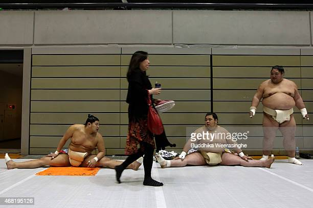 A woman walks past professional sumo wrestlers as they taake part in a training session during the Grand Sumo Tournament at the Himeji Chuo Gymnasium...