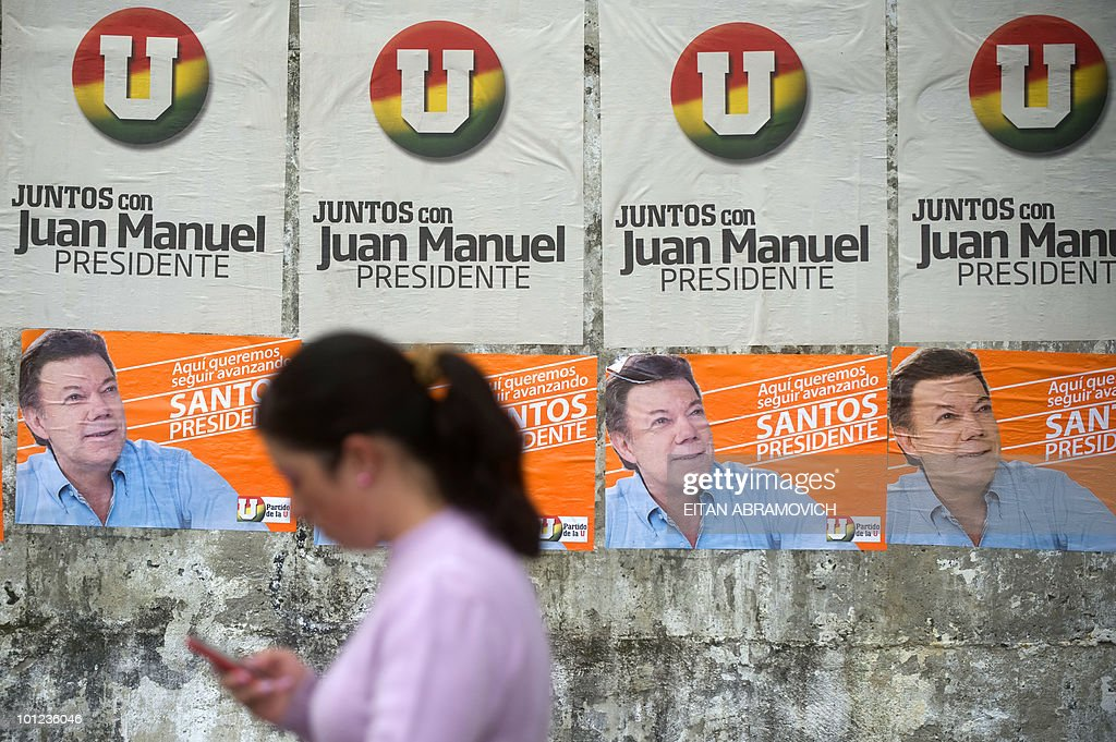 A woman walks past propaganda posters of Colombian presidential candidate for the ruling National Unity Party Juan Manuel Santos in Chipaque, Cundinamarca department on May 28, 2010. Colombia will hold presidential elections next May 30, and according to polls, a run-off election between Antanas Mockus for the Green Party and Juan Manuel Santos for the ruling National Unity Party, will take place on June 20. AFP PHOTO/Eitan Abramovich