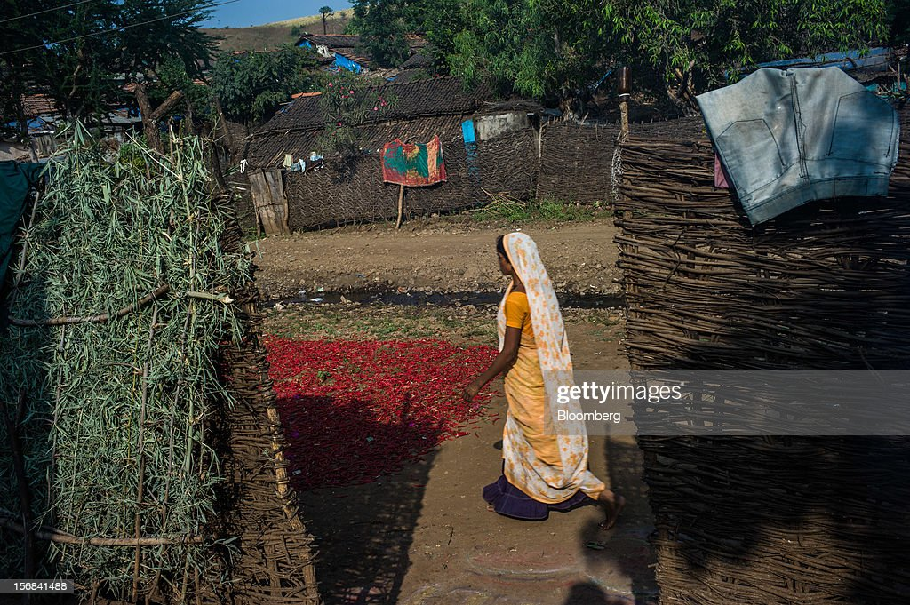A woman walks past red chili peppers left out for drying in Bhilkhera village, Maharashtra, India, on Thursday, Nov. 15, 2012. The Indian economy will expand 4.9 percent in 2012, the least in a decade, according to the International Monetary Fund. Photographer: Sanjit Das/Bloomberg via Getty Images