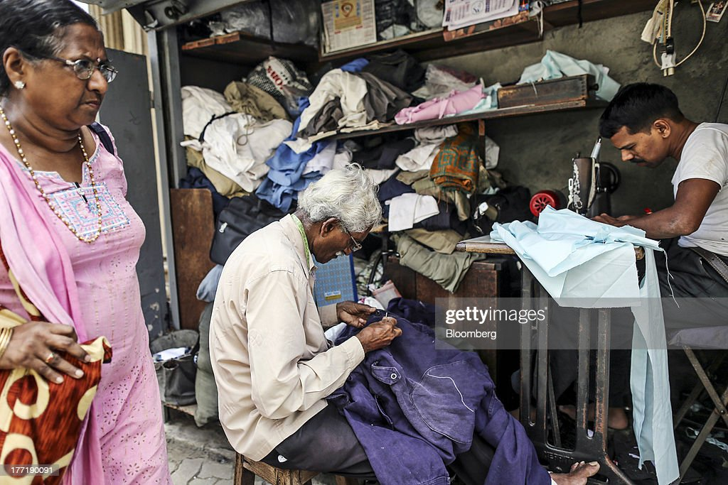 A woman walks past roadside tailors working at a stall in Mumbai, India, on Wednesday, Aug. 21, 2013. The prospect of an indecisive 2014 election in India is eroding confidence among global investors that the government can stop the rupees worst drop in more than two decades. Photographer: Dhiraj Singh/Bloomberg via Getty Images