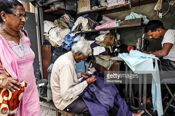 A woman walks past roadside tailors working at a stall in Mumbai India on Wednesday Aug 21 2013 The prospect of an indecisive 2014 election in India...