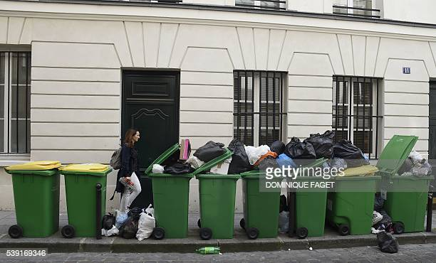 A woman walks past rubbish bins on the pavement on the SaintGermain Boulevard in the centre of Paris on June 10 2016 The piles of uncollected...