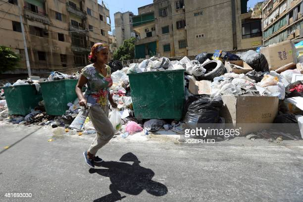 A woman walks past rubbish dusted with white poison powder to keep away the rats and insects piled up on a street in the Lebanese capital Beirut on...