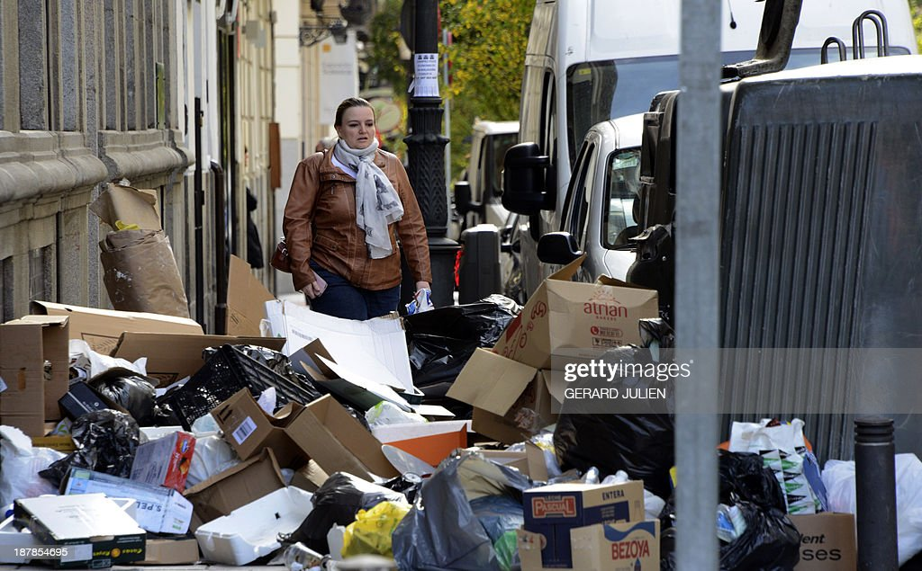A woman walks past rubbish in the centre of Madrid on November 13, 2013 during an open-ended strike by street-sweepers against layoffs and salary cuts. Rubbish keep piling up in the gutters of Madrid, on the ninth day of the strike by street-sweepers facing sackings and salary cuts, leaving its mark on the major tourist destination.