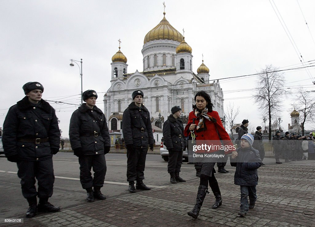 A woman walks past Russian police standing by Christ The Saviour Cathedral where Orthodox Russians are gathering to pay tribute to late Russian...