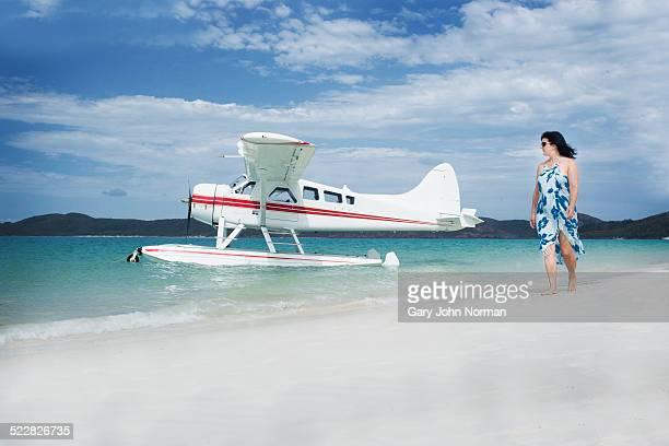 Woman walks past seaplane on tropical beach.