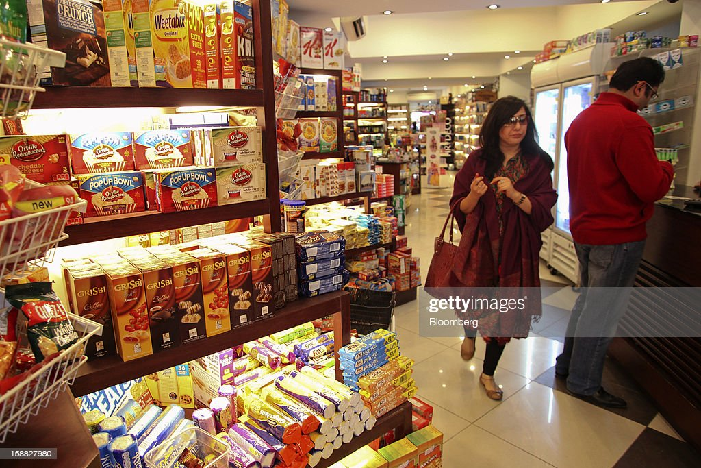 A woman walks past shelves of packaged foods at Shams supermarket in Islamabad, Pakistan, on Sunday, Dec. 30, 2012. Pakistan's economy will probably expand 3.5 percent in the 12 months through June, the International Monetary Fund forecast Nov. 29, less than the 4.3 percent predicted by the government. Photographer: Asad Zaidi/Bloomberg via Getty Images