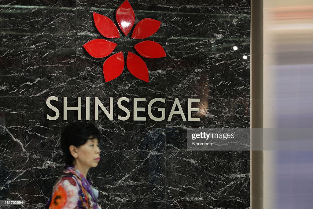 A woman walks past Shinsegae Co. signage displayed at one of the company's department stores in Seoul, South Korea, on Tuesday, Sept. 24, 2013. The South Korean economy faces headwinds, with record household debt and a sluggish housing market weighing on consumption. Photographer: SeongJoon Cho/Bloomberg via Getty Images
