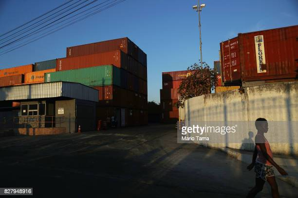 A woman walks past shipping containers in the Caju neighborhood which houses two forlorn shipyards along Guanabara Bay on August 8 2017 in Rio de...
