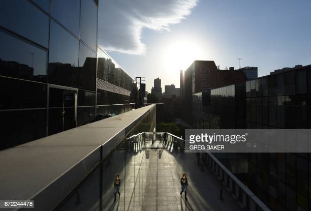 TOPSHOT A woman walks past shops in a mall in Beijing on April 24 2017 The International Monetary Fund on April 18 raised its economic growth...