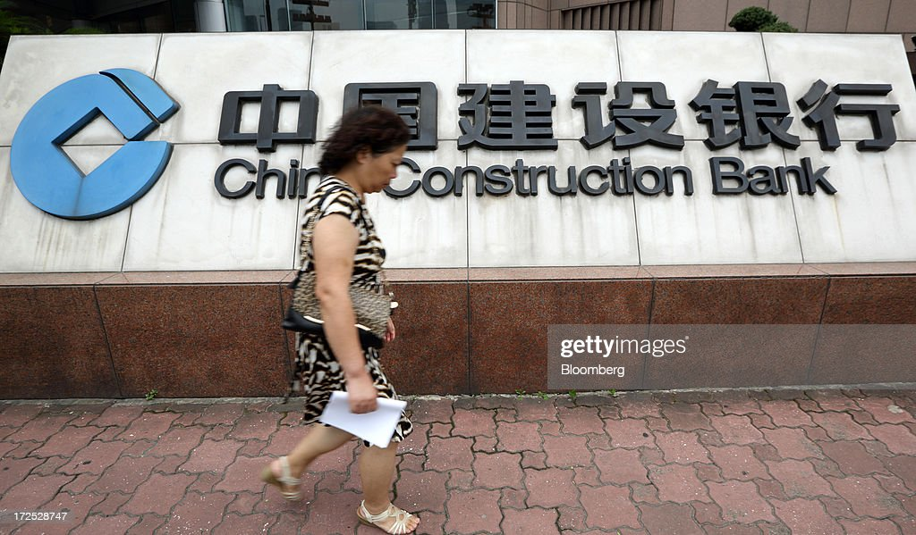 A woman walks past signage for China Construction Bank Corp. displayed outside a bank branch in Shanghai, China, on Monday, July 1, 2013. Chinese banks' valuations are close to their lowest on record as the nation's interbank funding crisis exacerbated investors' concern that earnings growth will stall and defaults may surge as the economy slows. Photographer: Tomohiro Ohsumi/Bloomberg via Getty Images