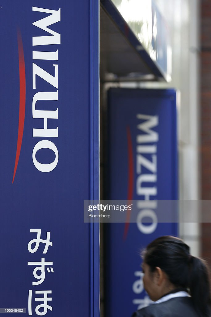 A woman walks past signage for Mizuho Financial Group Inc. in Tokyo, Japan, on Tuesday, Nov. 13, 2012. Mizuho Financial Group Inc. is scheduled to announce first-half earnings results on Nov. 14. Photographer: Kiyoshi Ota/Bloomberg via Getty Images