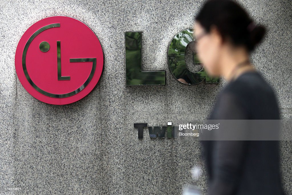 A woman walks past signage for the LG Twin Towers, which houses LG Corp. subsidiaries including LG Electronics Inc., LG Display Co., LG Chem Ltd. and LG Household & Health Care Ltd., in Seoul, South Korea, on Wednesday, July 24, 2013. LG Electronics, the worlds second-largest television maker, posted second-quarter profit that missed analyst estimates on slowing demand for sets and increased spending on marketing for smartphones. Photographer: Woohae Cho/Bloomberg via Getty Images