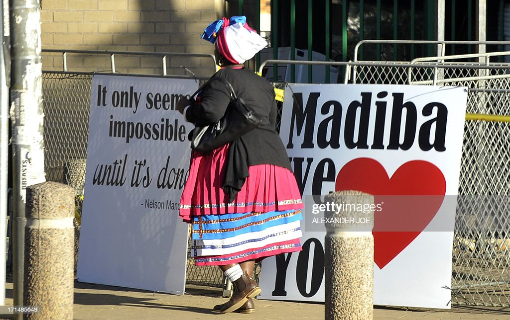 A woman walks past signs wishing well former South African president Nelson Mandela on June 25, 2013 outside of the Mediclinic heart hospital in Pretoria where Mandela is receiving treatment. Mandela's close family gathered today at his rural homestead to discuss the failing health of the South African anti-apartheid icon who was fighting for his life in hospital. Messages of support poured in from around the world for the Nobel Peace Prize winner, who spent 27 years behind bars for his struggle under white minority rule and went on to become South Africa's first black president.