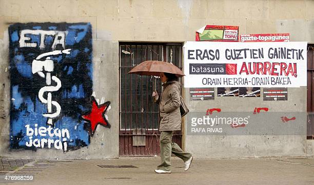 A woman walks past some banners and graffiti representing the proindependence armed Basque group ETA logo and supporting ETA's political wing banned...