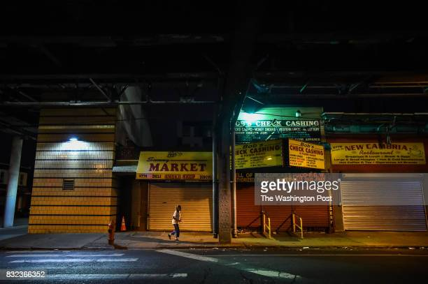A woman walks past store fronts along Kensington Ave on Thursday July 20 in Philadelphia PA