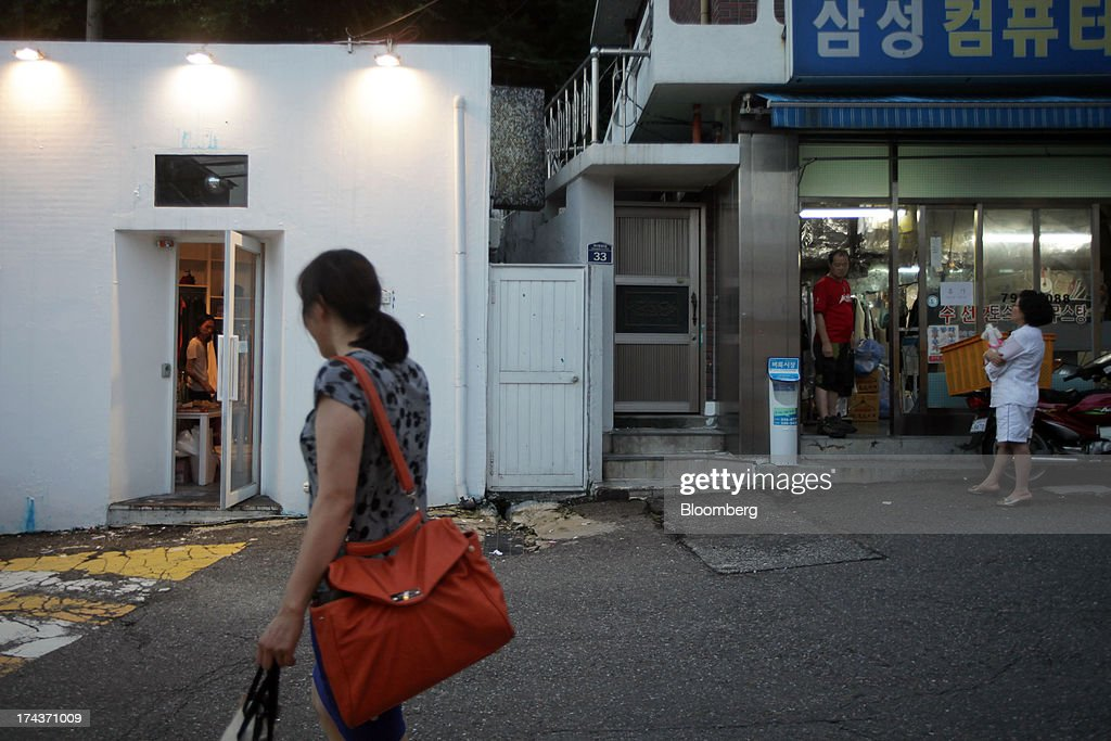 A woman walks past stores in the area of Hannam-dong in Seoul, South Korea, on Wednesday, July 24, 2013. South Koreas economy grew the most in more than two years, on stronger government spending and private consumption even as a slowdown in China clouds the outlook. Photographer: Woohae Cho/Bloomberg via Getty Images