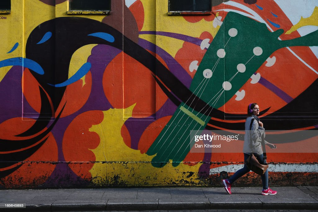 A woman walks past street art in the Temple Bar area on October 23, 2013 in Dublin, Ireland. Dublin is the capital city of The Republic of Ireland situated in the province of Leinster at the mouth of the River Liffey. The greater Dublin area has a population of around 1.5 Million people.